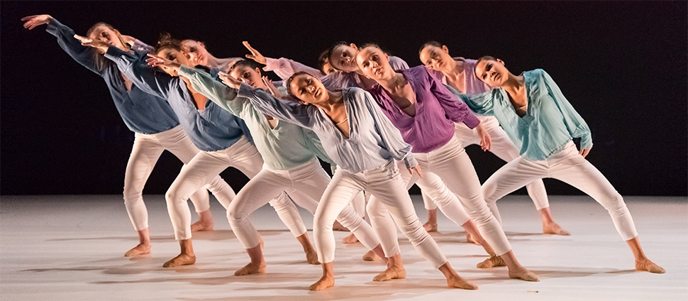 Group of dancers in white pants and differently colored tops
