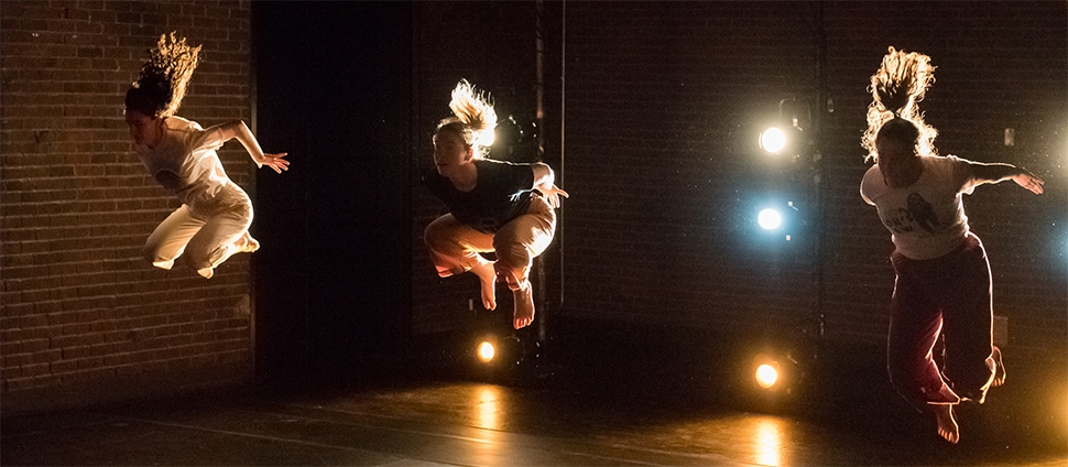 Three dancers mid-air in front of brick backdrops