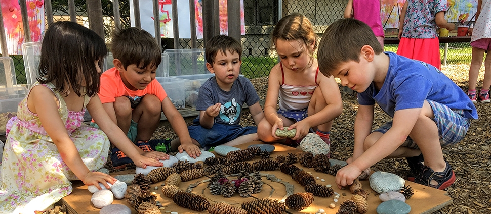Group of young children making art from pinecones