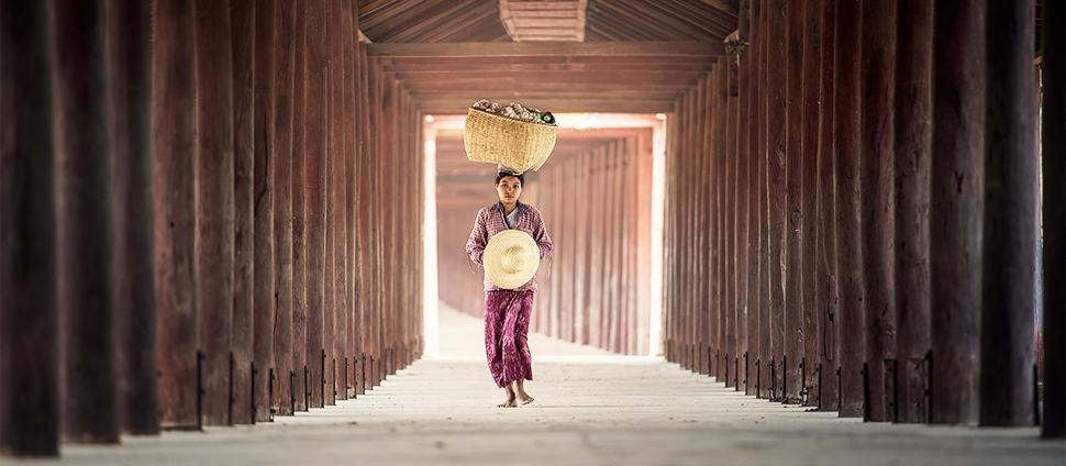 Photo of a woman carrying a basket on her head