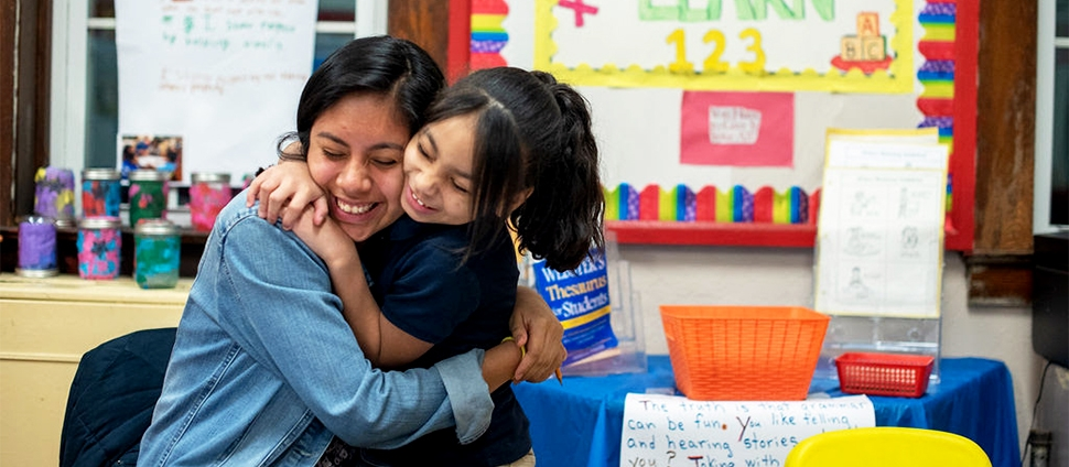 Smith student doing community service and hugging a child in school