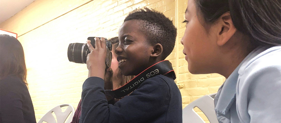 Smith student at a school with a child learning how to use a camera