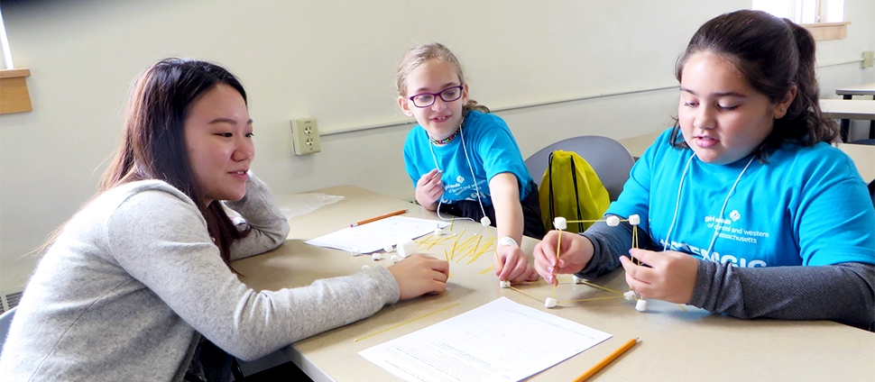 Smith student doing STEM outreach with two elementary school children