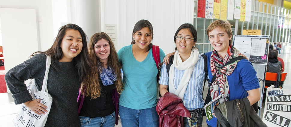 A group of smiling students posing in the Campus Center