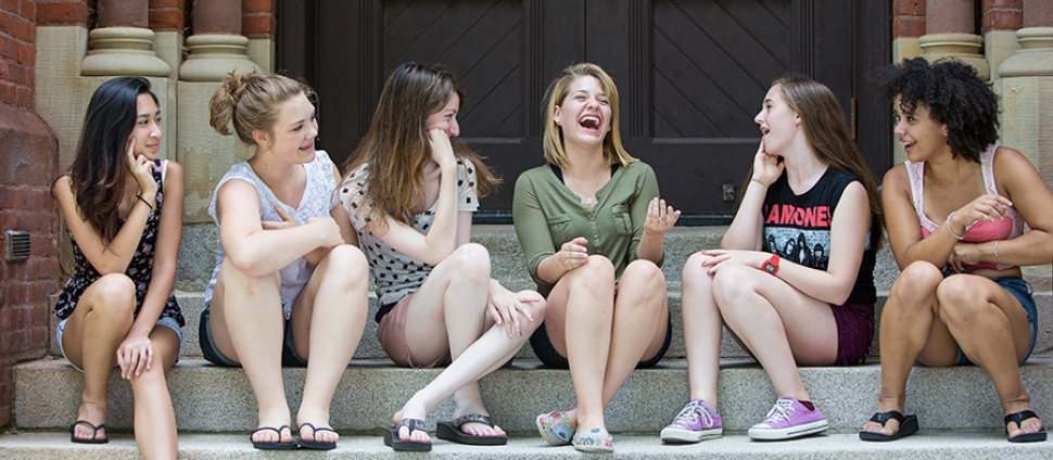 A group of young women sit together on Smith campus, during precollege summer programs