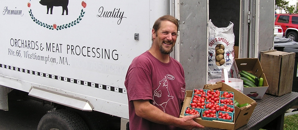 Man from local farm displays his fresh tomatoes from the back of a truck
