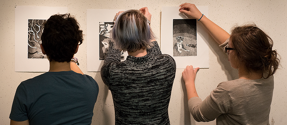 Three students hanging art on a gallery wall
