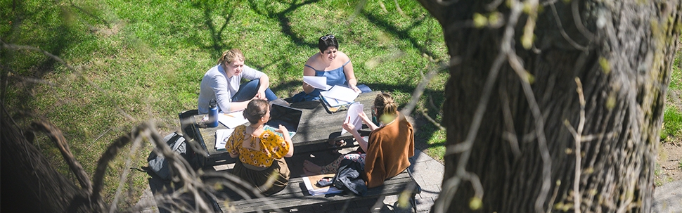 Students talking and sitting at a picnic table with computers and notebooks