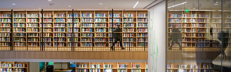 Students walking by rows of bookshelves visible on two floors in Neilson Library
