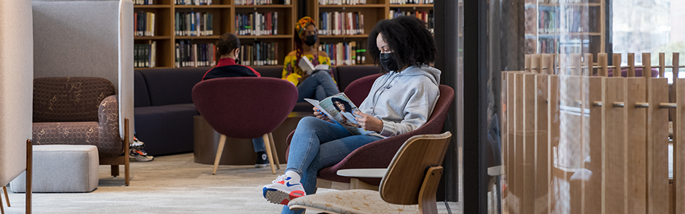 Student sitting in a chair reading a magazine, while a group of students studies at a table in the background.