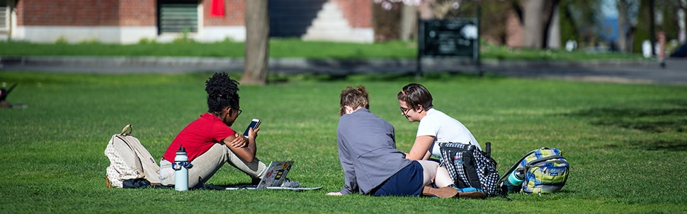 Three students sitting outside the Campus Center on the lawn