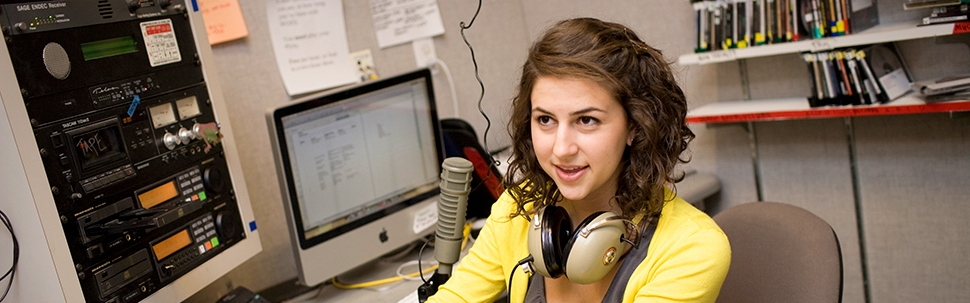 Student at the control board of the college radio station