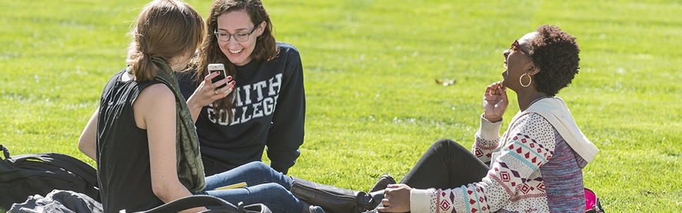 Three students sitting on the Campus Center lawn on a fall day