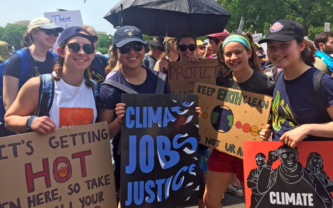 A group of students holding signs protesting for climate justice