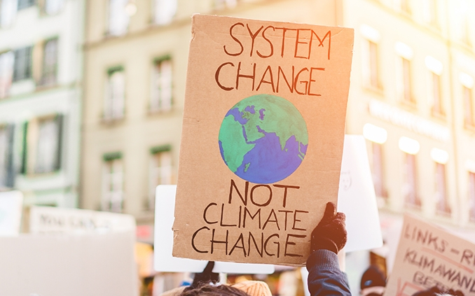 Sign at a protest reading System Change Not Climate Change