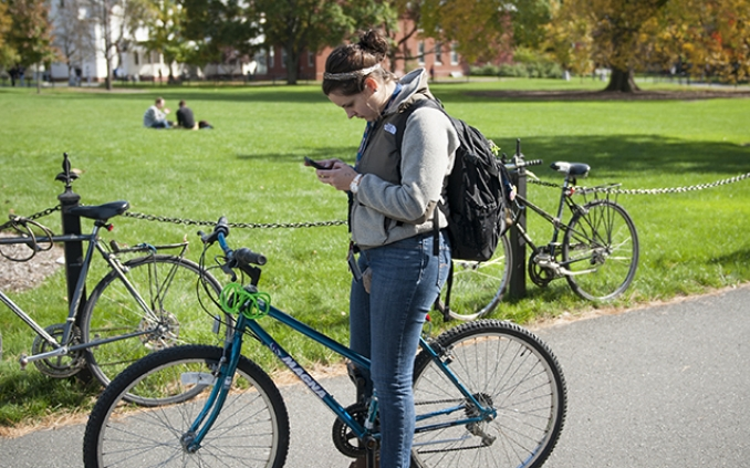 Girl looking at cellphone while riding a bike