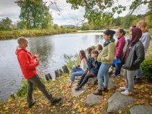 Reid Bertone-Johnson on a river bank teaching students