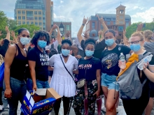 """Six friends—five black and one white— in masks standing next to each other in front of a citscape. T-shirts include """"Black Nerds Unite"""" and """"Melanin Poppin"""""""
