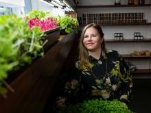 Jessie Banhazl next to hydroponic vegetables