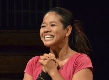 Phounam Pin smiling broadly on a stage