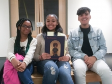Three students of color seated and smiling at the camera. The middle person holds a copy of the exhibit book Black Refractions