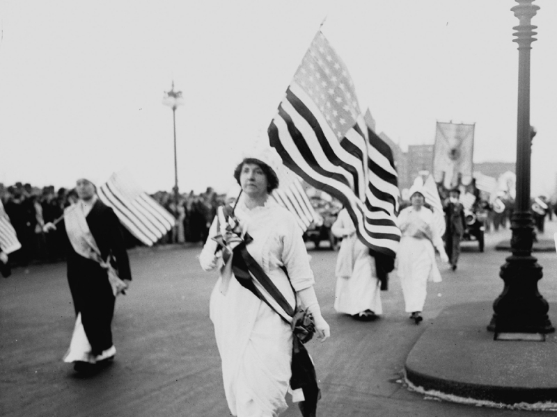 A woman in white carrying an American flag in the 1913 parade on Washington