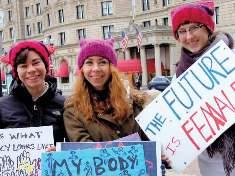 """Three smiling people in pink pussy hats with signs including """"The Future is Female"""""""