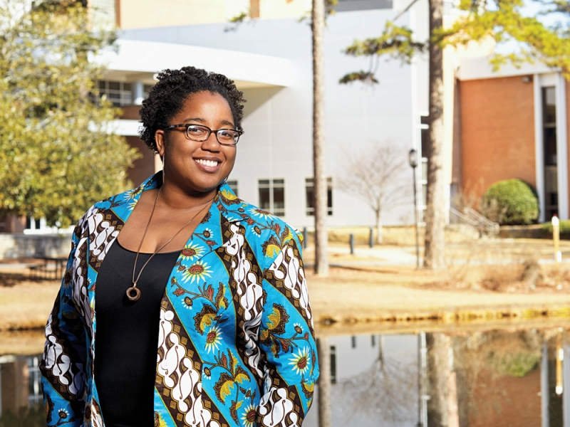 A black woman in a bright blue patterned jacket standing in front of a pond and brick building
