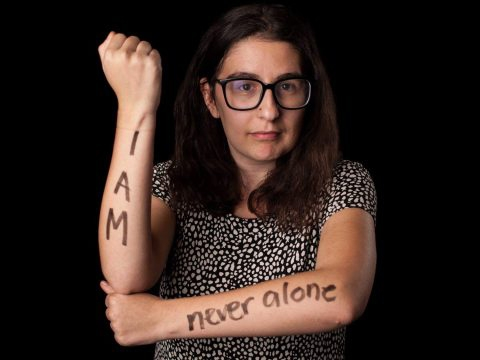 """Becca Damante '17 with the words """"I Am Never Alone"""" marked on her arms"""