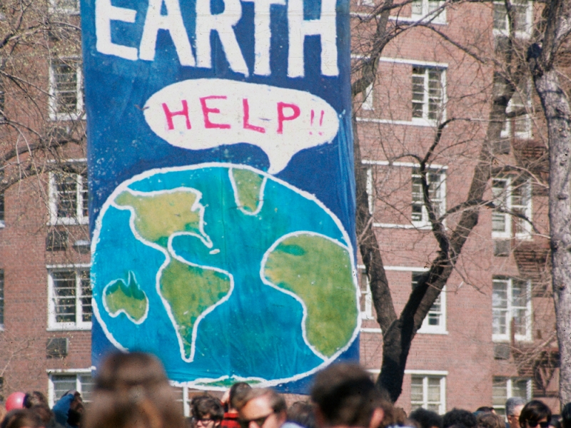 """Earth Day 1970. A large banner with the globe saying """"help"""" and EARTH in large letters. Below it is a large crowd."""