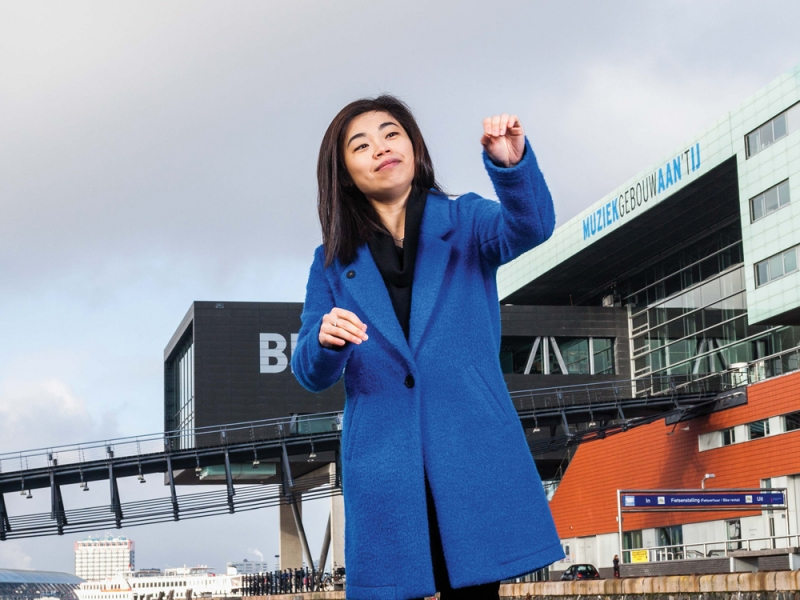 Elim Chan, who appears east Asian, in a bright blue coat and her hands in a conducting posture