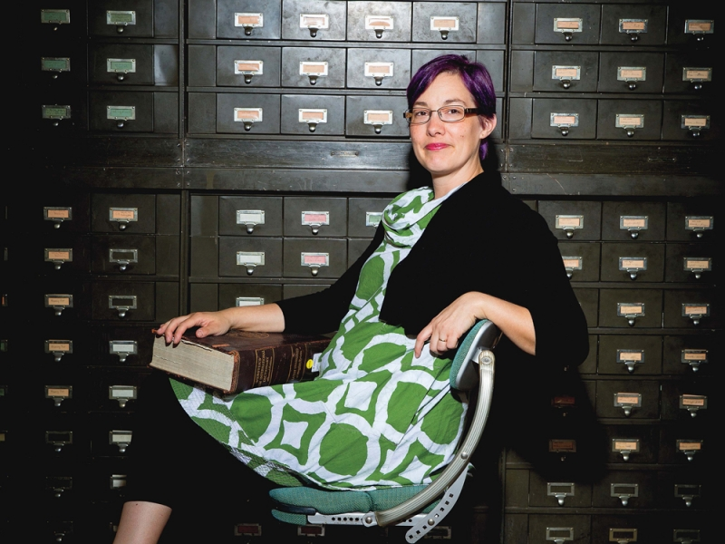 Kory Behny Stamper in a green dress with purple hair. She holds a large rare book in front of a bank of card catalogs