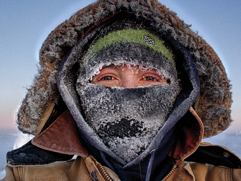 Marie McLane in many layers of warm clothes with ice on her scarf and hat, with only her eyes visible