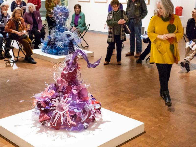 Viewers standing around sculpture by Aurora Robson