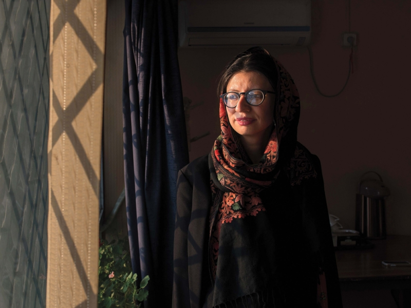 Sharharzad Akbar wearing a red and black head scarf with black glasses looking out a window
