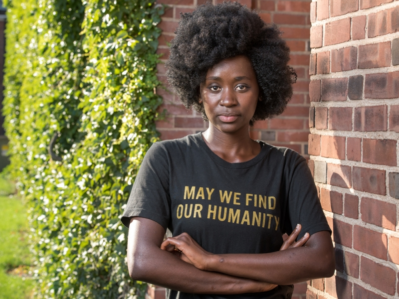 """Hawa Tarawally leaning against a brick wall. Her shirt says, """"May we find our humanity."""""""