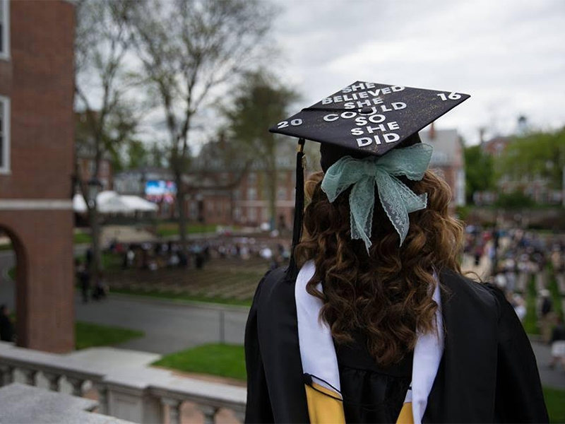"Student in commencement cap reading ""She believed she could so she did"""