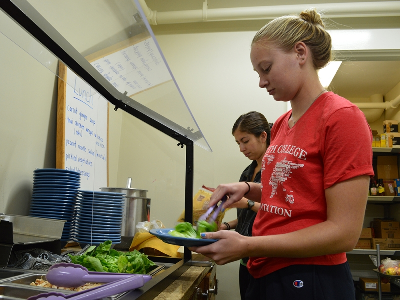 Two students make selections from a buffet
