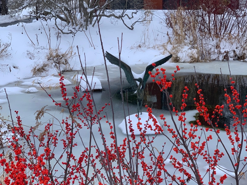 Heron statue on a frozen pond with red winter berries