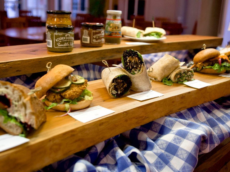Row of sandwiches and wraps on a wood shelf with condiments on another shelf behind and above
