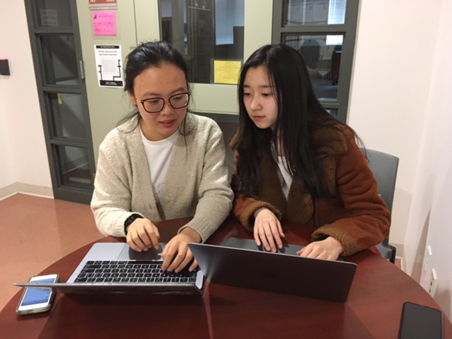 Yuqing Geng '21 (left) and Qiaqia Ji '20 review stock histories in preparation for the Midwest Trading Competition in Chicago. Isabella Zhu '20 is also on the team.