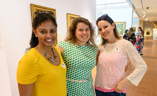 Three alumnae standing close together and smiling in the Smith College Museum of Art