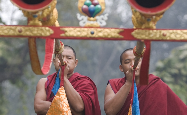 Two monks blowing into large horns, Tibet