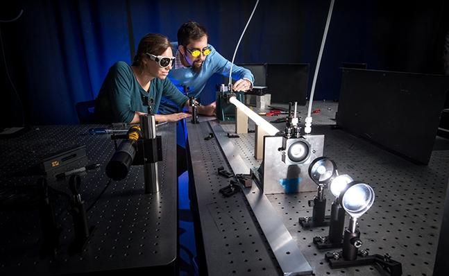 Assistant Professor Andrew Berke with student in laser lab