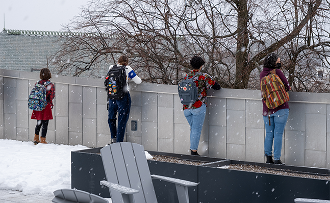 Students standing on the roof of Neilson library, looking over the edge