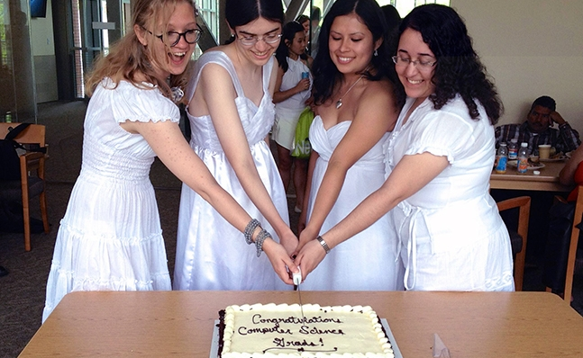 Four computer science grads in Commencement dresses cutting a cake