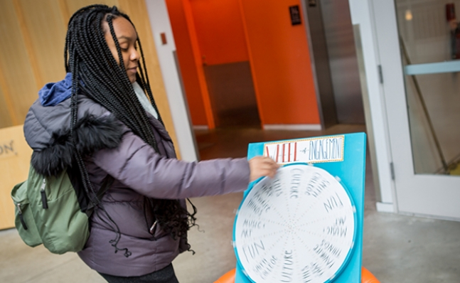 "Student spinning the ""Wheel of Engagement"" at the Campus Center"