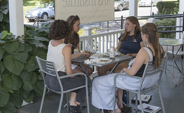 Photo of group meeting on the porch of the Kahn Institute