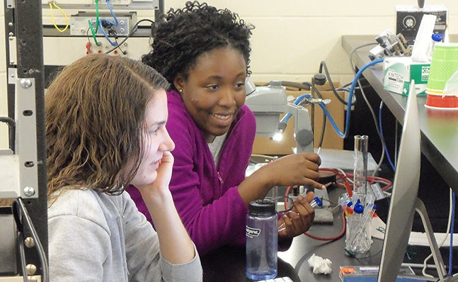 Two students at computer in lab
