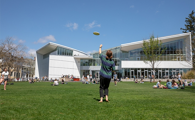 Students playing frisbee outside on campus